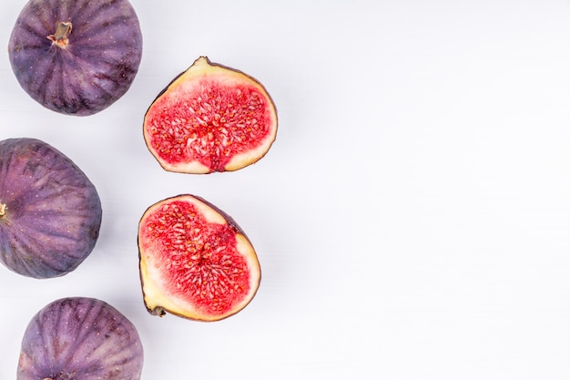Purple fresh whole and sliced figs on white background