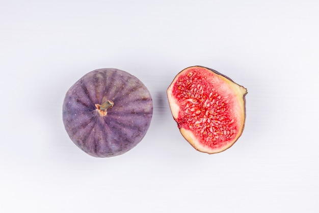 Purple fresh whole and sliced half figs on white background