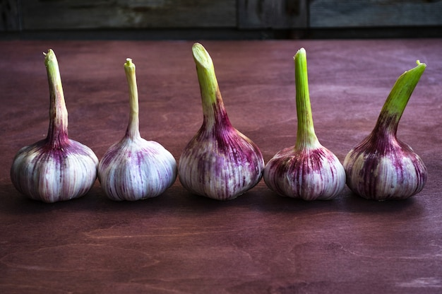 Purple garlic on a brown wooden table.