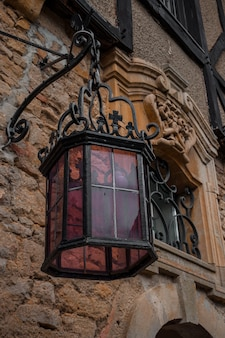 Фиолетовый стеклянный наружный светильник на старом здании