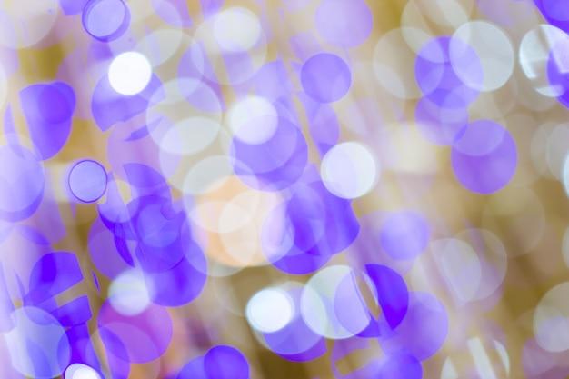 Purple glitter lights defocused christmas bokeh blur city background in party night light decoration in soft purple