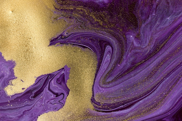 Purple and golden mixed inks abstract dark background.