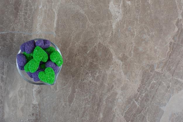 Caramelle viola e verdi a forma di cuore in una ciotola di vetro.