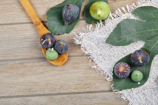 Fichi viola e verdi sulla tavola di legno con una tovaglia bianca, una foglia e un cucchiaio di legno.