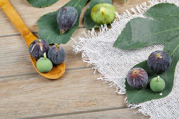 Fichi viola e verdi sulla tavola di legno con una tovaglia bianca e una foglia, un cucchiaio di legno.