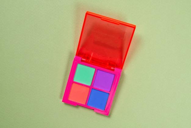 녹색 배경에 보라색, 녹색, 주황색 및 파란색 아이 섀도우 팔레트. 조립. 네온 색상입니다.