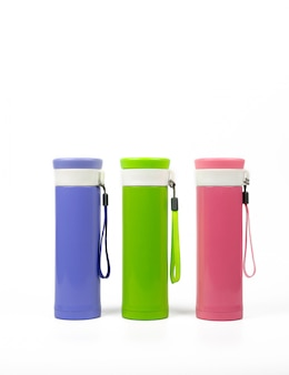 Purple, green and pink thermos bottles isolated on white background with copy space