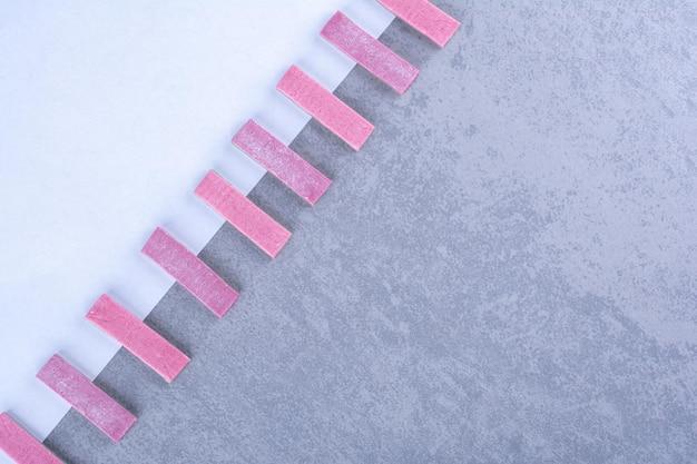 Фиолетовые палочки жевательной резинки по диагонали выровнены по краю бумажного листа на мраморной поверхности.