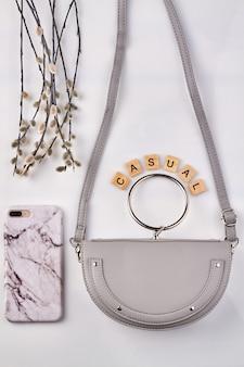 Фиолетовая сумочка и модный чехол для телефона. филиал ивы на белом фоне.