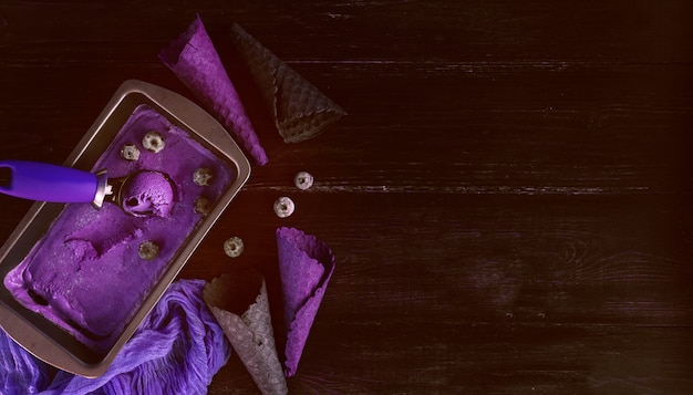 Purple ice cream with a spatula for ice cream on a dark wooden background with waffle cups