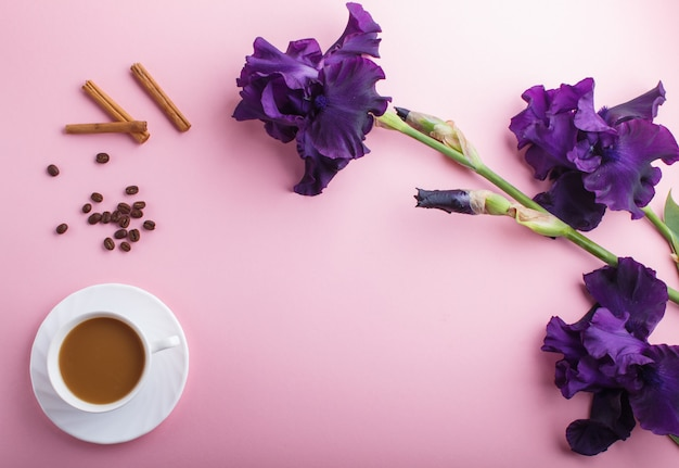 Purple iris flowers and a cup of coffee on pastel pink