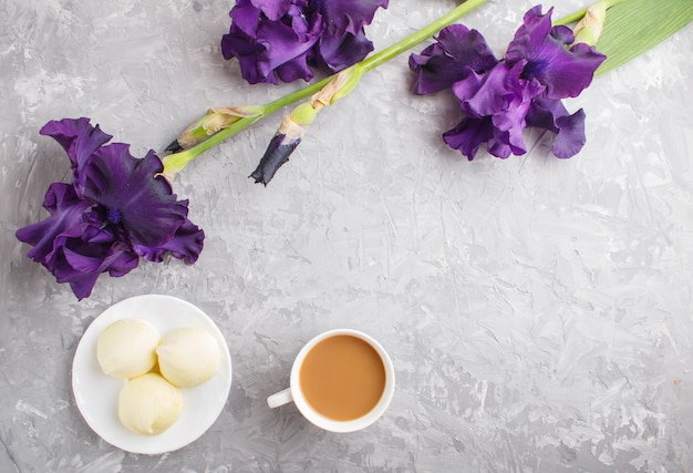 Purple iris flowers and a cup of coffee with marshmallow on a gray concrete background.