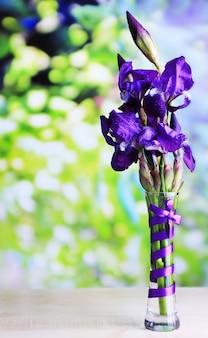 花瓶、木製テーブル、ライトに紫色のアイリスの花