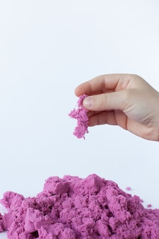 Purple kinetic sand in hand isolated on a white background. colored sand for modeling for children