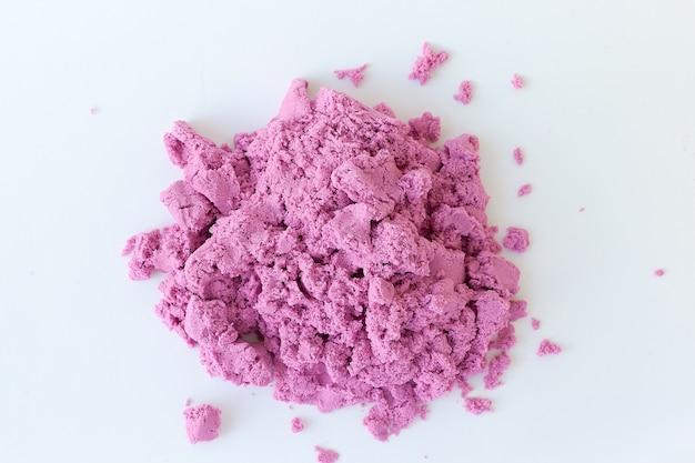 Фиолетовый кинетический песок в руке, изолированные на белом фоне. цветной песок для лепки для детей.