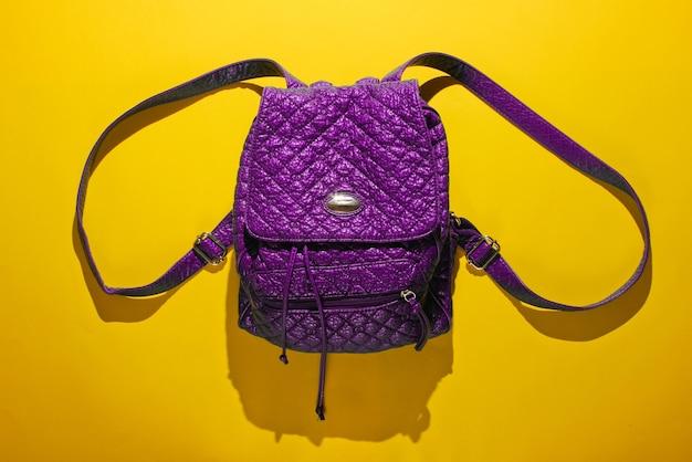 黄色の背景にストラップ付きの紫色の革のバックパック。トップビュー、ミニマリズムファッション
