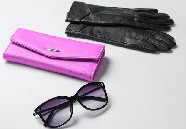 Фиолетовый кожаный кошелек, солнцезащитные очки, перчатки крупным планом на белом фоне