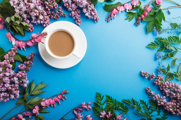 Purple lilac and bleeding heart flowers and a cup of coffee on pastel blue.