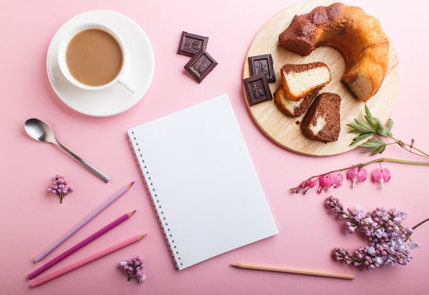 Purple lilac and bleeding heart flowers and a cup of coffee with notebook, cake and colored pencils