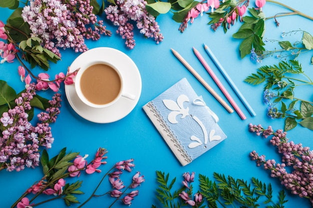 Purple lilac and bleeding heart flowers and a cup of coffee with notebook and colored pencils on pastel blue background