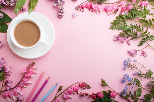 Purple lilac and bleeding heart flowers and a cup of coffee with notebook and colored pencils on pastel pink.