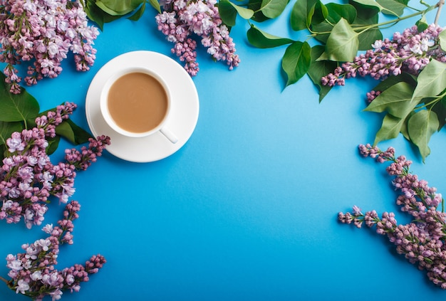 Purple lilac flowers and a cup of coffee on pastel blue.