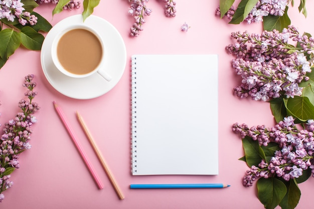 Purple lilac flowers and a cup of coffee with notebook and colored pencils on pastel pink background