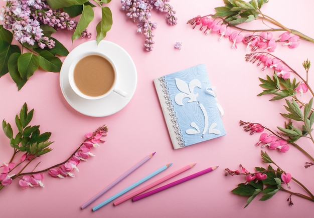 Purple lilac flowers and a cup of coffee with notebook and colored pencils on pastel pink background.