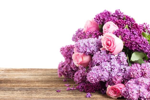 Фиолетовые цветы сирени на деревянном столе, изолированные на белом фоне