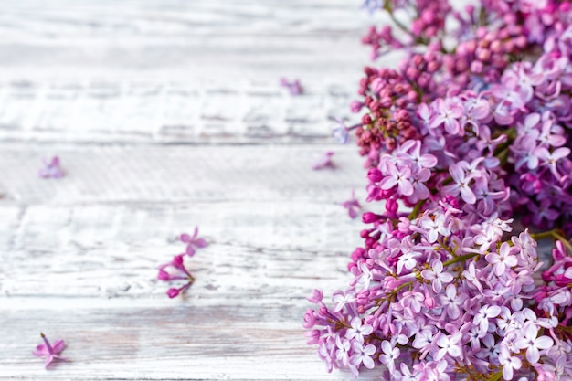 Фиолетовая сирень весенние ветви цветущей сирени праздничный букет цветов с копией пространства. фиолетовая ветвь сирени на столе, цветочный натюрморт на серой деревянной предпосылке.