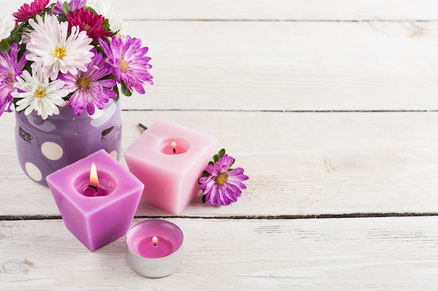 Purple lit candles and pink garden flowers