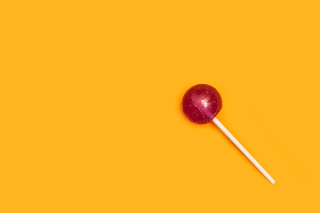 Purple lollipop on a yellow background in a top view