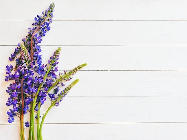 白い木製のテーブルの上の紫色のルピナスの花。