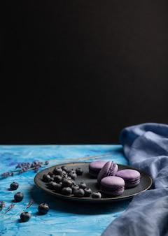 Purple macarons or macaroons cakes with blueberries on ceramic plate on a blue and black background.