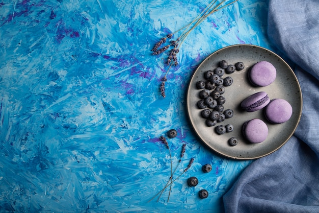 Purple macarons or macaroons cakes with blueberries on ceramic plate on a blue concrete background.
