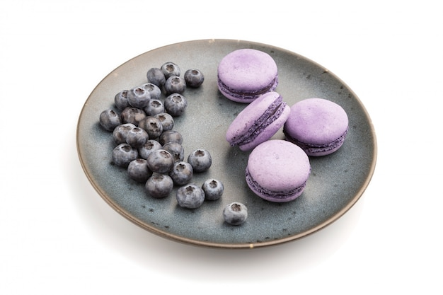 Purple macarons or macaroons cakes with blueberries on ceramic plate isolated on white background.