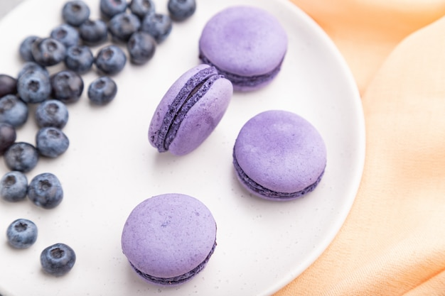 Purple macarons or macaroons cakes with blueberries on white ceramic plate on a gray concrete background. top view, selective focus.