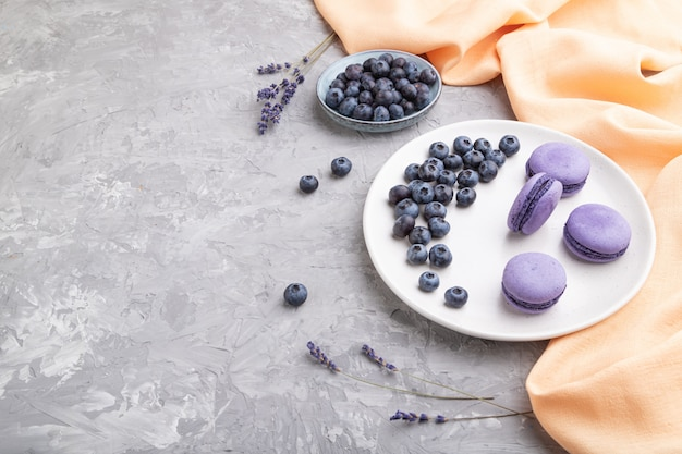 Purple macarons or macaroons cakes with blueberries on white ceramic plate on a gray concrete background.