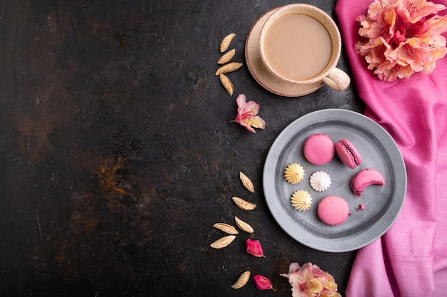 Purple macarons or macaroons cakes with cup of coffee on a black concrete surface and pink textile