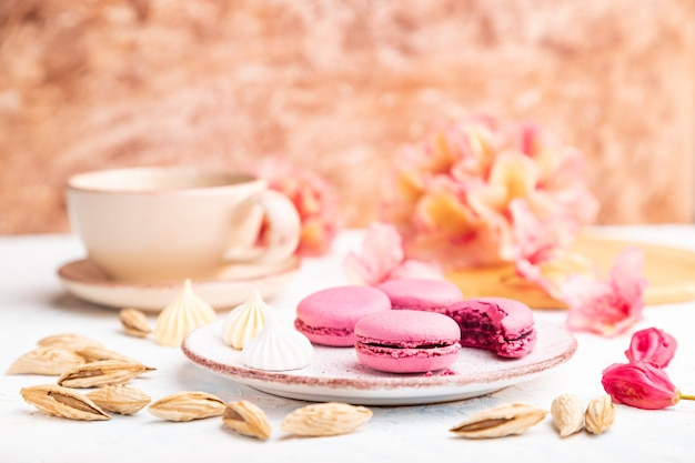 Purple macarons or macaroons cakes with cup of coffee on a white and brown concrete surface decorated with flowers