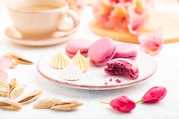 Purple macarons or macaroons cakes with cup of coffee on a white concrete background decorated with flowers.