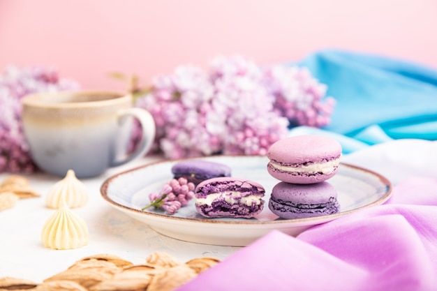 Purple macarons or macaroons cakes with cup of coffee on a white concrete background. side view, selective focus.