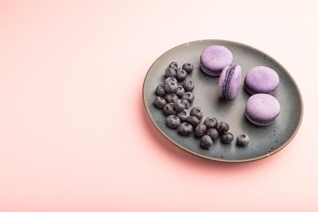 セラミックプレートにブルーベリーと紫のマカロンまたはマカロンケーキ。側面図、クローズアップ、コピースペース。