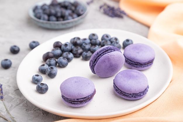 灰色のコンクリートテーブルの上の白いセラミックプレートにブルーベリーと紫のマカロンまたはマカロンケーキ。側面図、クローズアップ。
