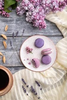 회색 나무 표면과 흰색 리넨 섬유에 커피 한잔과 함께 보라색 마카롱 또는 마카롱 케이크
