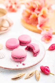 Фиолетовый macarons или миндальное печенье торты с чашкой кофе на белом фоне конкретных. взгляд со стороны, конец вверх, селективный фокус.