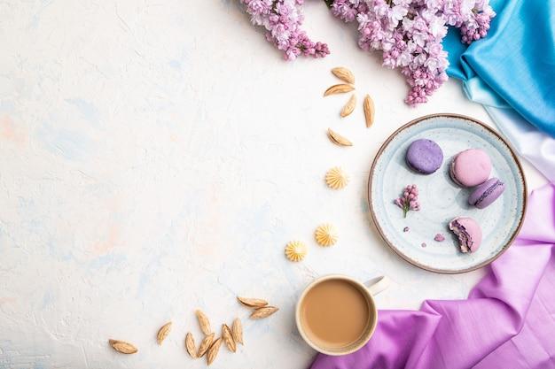 Фиолетовые макароны или торты из макарон с чашкой кофе на белой бетонной поверхности и пурпурно-синей ткани