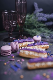 Purple macaroons falling from the decorative glass on dark textured background