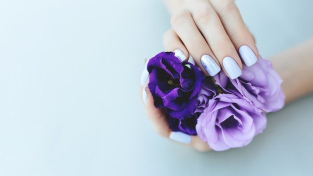 Purple manicure on a plain background with flowers
