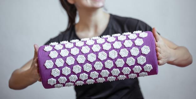 女性の手の紫色のマッサージ鍼灸枕と白いマッサージのヒント